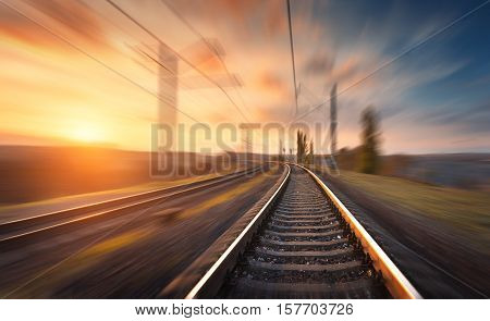 Railroad In Motion At Sunset. Blurred Railway Station