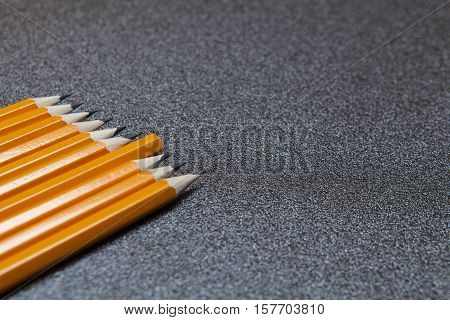Ten sharpened pencils on gray speckled background with one inverted concept like think different stand out from the crowd close up view