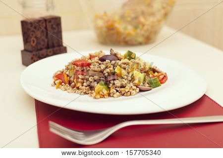 Close up of spelt salad with vegetables served on white plate in restaurant healthy food selective focus