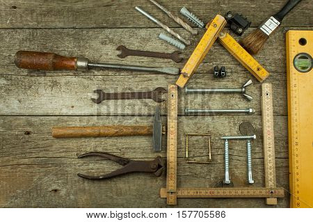 Plans to build a house. Rustic wooden background. Tools for builders. Architect designing a house for a young family. House from nails and screws. Needed for building. Ideas about building a house.