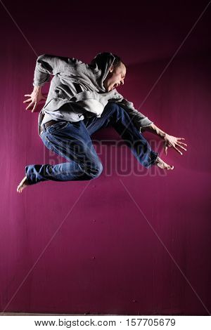 Man in motion on pink background studio shot