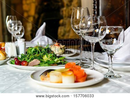 Served for holiday banquet restaurant table with dishes, snack, cutlery, wine and water glasses, european food