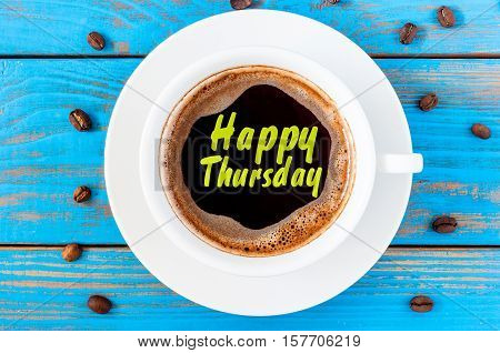 Happy thursday word on coffee cup at blurred blue wooden background with beans.