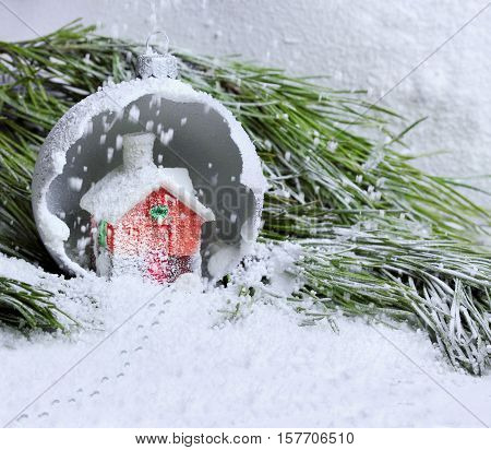 Miniature Christmas House In Crushed Ball On The Pine Branch .snow Everywhere And Tracks On Snow.see