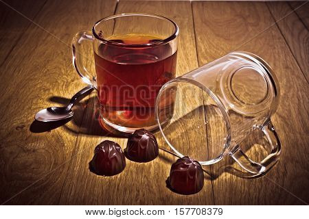 Tea cup spoon chocolate candy and empty cup made of glass