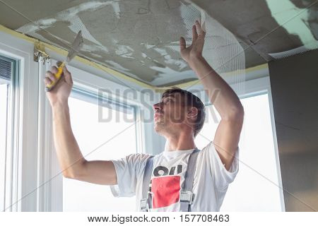 Thirty years old manual worker with wall plastering tools renovating house. Plasterer renovating indoor walls and ceilings with float and plaster. Wall mash installation. Construction finishing works. poster