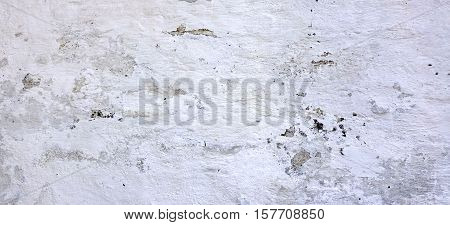 Dark Wall With Dirty White Grey Scratched Plaster Horizontal Background. Old Brickwall With Peel Dirty White Stucco Texture. Retro Vintage Wreck Concrete Wall. Decay Rough Abstract Banner Surface.