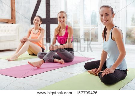 We are active. Three happy athletic girls posing after having group training while spending time in gym.