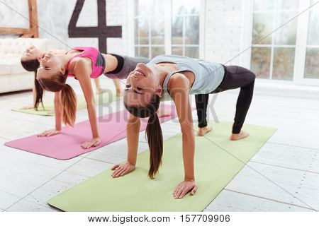 Work till the end. Three happy young girls having group fitness exercises and training hard while spending day in a gym.