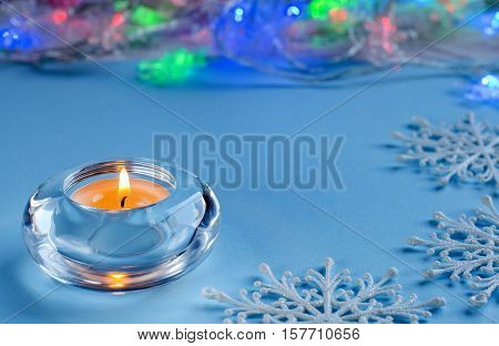 Christmas And Winter Holidays. Candle On Blue Background.