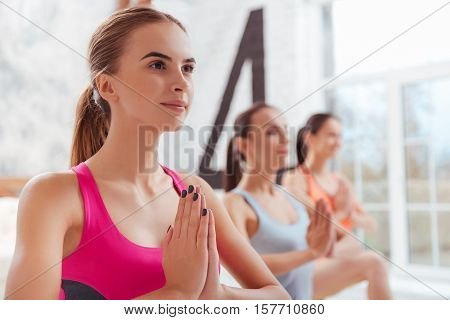 Keep your thoughts clear. Three concentrated young women having yoga classes while training in groups and relaxing.