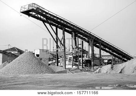 Rock crusher machine. Equipment of gravel plant. Black and white photography