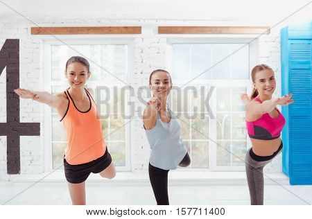 Do it together. Three joyful young women posing after training and spending morning in fitness studio.