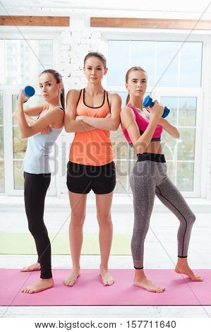 Train hard. Three athletic young women holding dumbbells and posing after having workout in a gym.