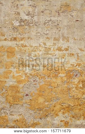 Brick Wall With Damaged  Shabby Yellow Plaster Vertical Background Texture