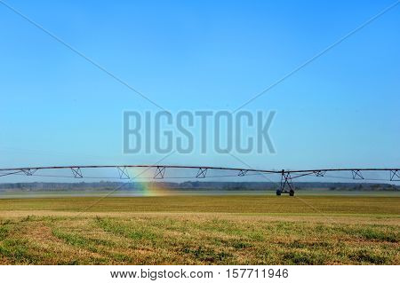 Agriculture irrigation equipment produces spray rainbow. Field is in Southern Arkansas. Image could represent the hope for the future of agriculture.