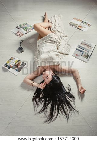 Gorgeous woman while lying on a carpet among a magazines in the living room.