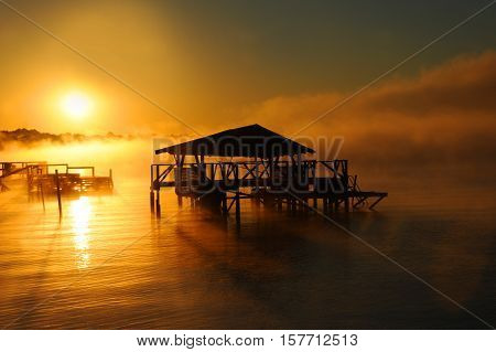 Early morning mist rises from Lake Chicot in Lake Village Arkansas. Wooden dock and boat house are silhouetted. Golden light covers lake.