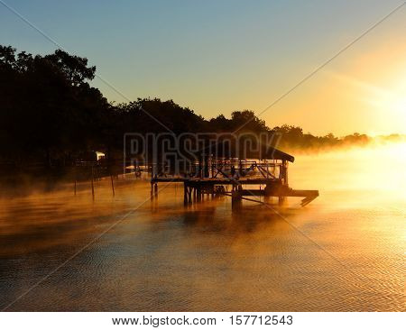 Golden light tints water and wooden dock gold as the sunrise hits Lake Chicot in Eastern Arkansas. Fog surrounds boat house and surface of lake.