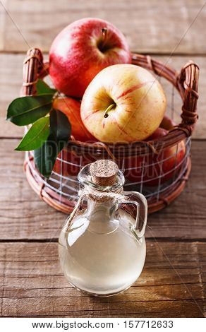 Apple cider vinegar and basket of apples over rustic wooden background