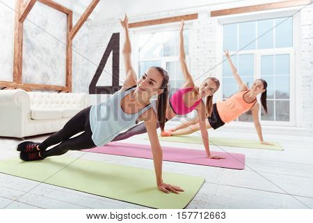 I love my hobby. Three active women enjoying sport while having training and spending time in a gym.