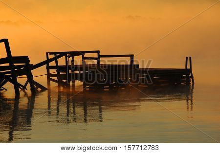 Rotting pier is surrounded by the golden light of dawn on Lake Chicot in Lake Village Arkansas.
