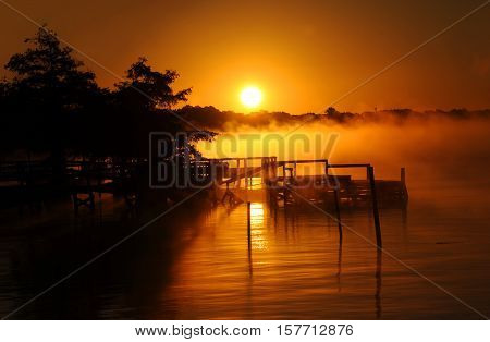 Golden morning dawns over Lake Chicot in Eastern Arkansas. Fog rises from calm surface of water and light silhouettes old wooden dock.