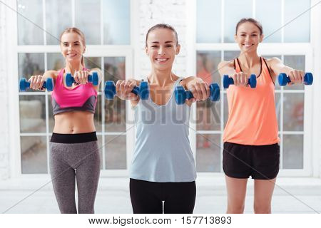 Strong arms. Three smiling young women using dumbbells while training and spending day in fitness studio.