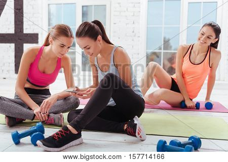 Time to have rest. Three young delighted women relaxing after having workout and sitting in a gym.