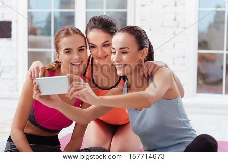 We are beautiful. Three pretty young women making selfie after doing exercises and training in a gym.