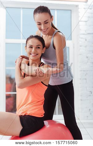 Help and counsel. Two young pretty women stretching muscles together after having workout and enjoying the results.