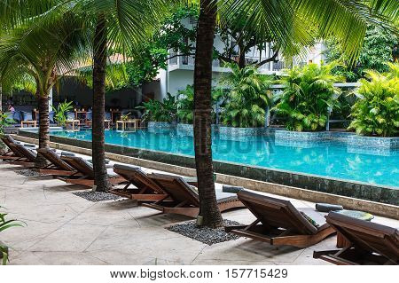 Sunbeds with towels near pool with blue water