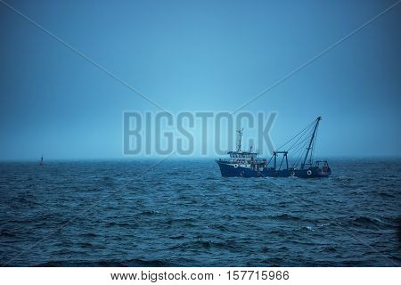 Trawler fishing boat sailing in open waters on a cold and foggy morning sunrise