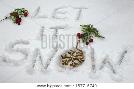 Christmas Winter wonderland Let it Snow words hand written in first snowfall freshly fallen in winter season with Christmas holiday theme including pine branches winter berries and snowflake Christmas tree ornament made of wood