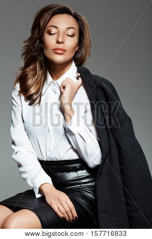 Young beautiful confident woman in black and white suit sitting over grey background. Eyes closed.