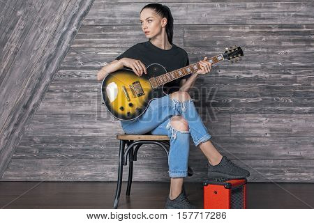Attractive caucasian girl with electric sunburst guitar sitting on amplifier in wooden room. Music concept