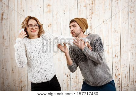 Young handsome man unnerve his girlfriend speaking on phone over wooden background. Copy space.