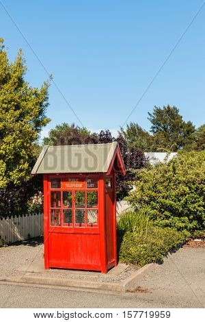 closeup of old red telephone booth in garden