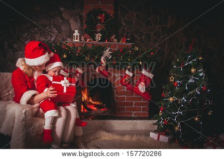 Mother and son are sitting near fireplace and christmas tree. Family look into a gift box.