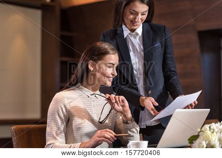 Friendly workers. Delighted young female colleagues working together and discussing project while spending time in an office.