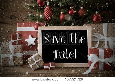 Chalkboard With English Text Save The Date. Nostalgic Card For Seasons Greetings. Christmas Tree With Balls And Snowflakes. Gifts In The Front Of Wooden Background.
