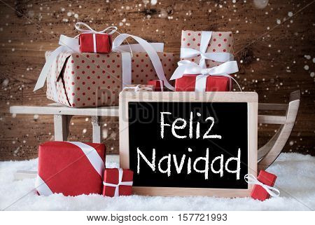 Chalkboard With Spanish Text Feliz Navidad Means Merry Christmas. Sled With Christmas And Winter Decoration And Snowflakes. Gifts And Presents On Snow With Wooden Background.