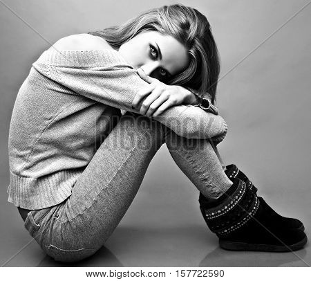 Young attractive woman on casual clothes siting on studio floor. Black-white photo.