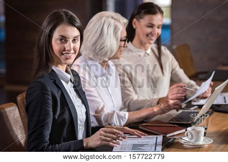 Till the end. Female concentrated young colleagues and their elderly boss working together and doing project while sitting in an office.