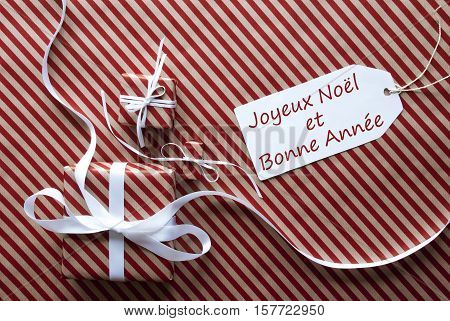 Two Gifts Or Presents With White Ribbon. Red And Brown Striped Wrapping Paper. Christmas Or Greeting Card. Label With French Text Joyeux Noel Et Bonne Annee Means Merry Christmas And Happy New Year