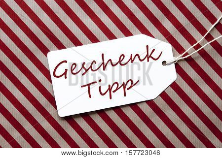 German Text Geschenk Tipp Means Gift Tip. One Label On A Red And Brown Striped Wrapping Paper. Textured Background. Tag With Ribbon.