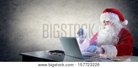 Santa Claus Writing With Laptop On The Desktop