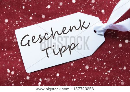 German Text Geschenk Tipp Means Gift Tip. One White Label On A Red Textured Background. Tag With Ribbon And Snowflakes.