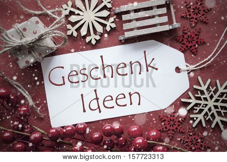 German Text Geschenk Ideen Means Gift Ideas. Nostalgic Christmas Decoration Like Gift Or Present, Sleigh. Card For Seasons Greetings With Red Paper Background.
