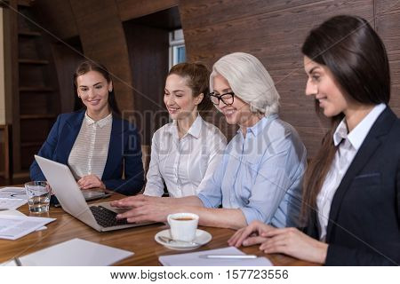 Inspiration in routine. Delighted female friendly colleagues working together while making project and sitting in an office.